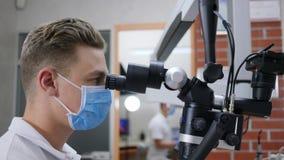 Laboratoriumforskaren i medicinsk maskering ser till och med mikroskopet i klinik arkivfilmer