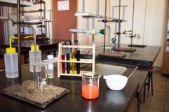 Laboratoriumglasföremål med röd flytande som är klar för filtrering Arkivbild