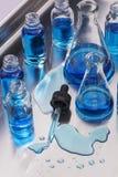 Laboratoriumglasföremål och spilld provvätska med droppglassen Arkivfoto