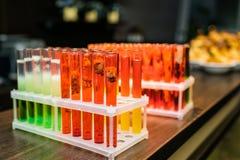 Laboratoriumglaswerk met alcoholcocktail op chemische partij Stock Foto's