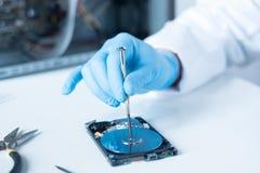 Laboratoriumingenieur die aan gebroken harde schijf werken Stock Foto
