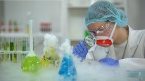 Laboratoriummedewerker die door vergrootglas flessen bekijken die rook, laboratorium uitzenden stock videobeelden