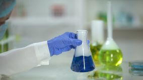 Laboratoriummedewerker die reactie in fles met blauwe substantie controleren die rook uitzenden stock footage