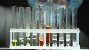 Laboratoriummedewerker die rode vloeistof in reageerbuis toevoegen, die geheim wetenschapsonderzoek leiden stock videobeelden
