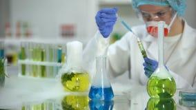 Laboratoriumonderzoeker die blauwe vloeibare substantie in buis met groene installatie, test toevoegen stock footage