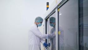 Laboratoriumteknikeren sätter saker i skåpet stock video