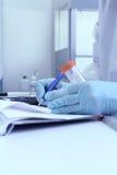 Laboratoriumteknikeren skriver provresultat från labb Royaltyfria Bilder