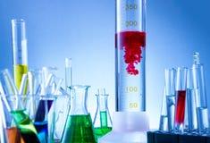Laboratoriumutrustning, flaskor som fylldes med färgrika flytande, röd flytande, reagerade Royaltyfria Bilder