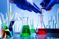 Laboratoriumutrustning, massor av exponeringsglas fyllde med färgrika flytande, den hällda handen Royaltyfri Fotografi