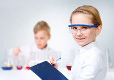 Laboratory assistant. A little girl in protective glasses making notes and looking at camera Stock Images