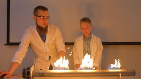 Laboratory assistant with boy makes experiment with fiery loudspeaker. Boy and laboratory assistant makes experiment with fiery stereo speaker. The fire is stock video footage