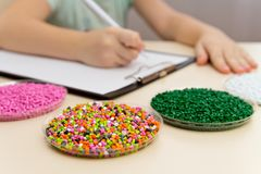 Laboratory assistant inspections plastic pellets for industry. Plastic raw materials in granules . Polymer, plastic resin. Laboratory assistant checks the royalty free stock photo