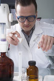 Laboratory assistant pours liquid from a bottle Royalty Free Stock Image