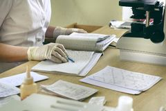 The laboratory assistant records the results of the tests in the log, the microscope and test results on the table royalty free stock image