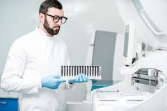 Laboratory assistant with test tubes in the laboratory. Male laboratory assistant in uniform holding test tubes near the analizer machine at the laboratory Royalty Free Stock Images