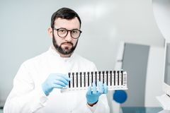 Laboratory assistant with test tubes in the laboratory. Male laboratory assistant in uniform holding test tubes near the analizer machine at the laboratory Stock Image