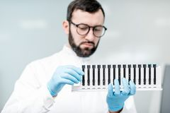 Laboratory assistant with test tubes in the laboratory. Male laboratory assistant in uniform holding test tubes near the analizer machine at the laboratory Royalty Free Stock Photo