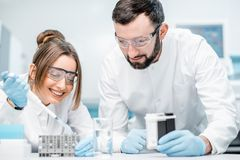 Laboratory assistants working in the medical laboratory. Laboratory assistants in uniform and protective glasses working with test tubes in the medical Royalty Free Stock Photo