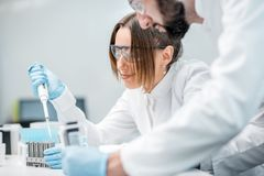 Laboratory assistants working in the medical laboratory. Laboratory assistants in uniform and protective glasses working with test tubes in the medical Stock Photo