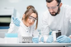 Laboratory assistants working in the medical laboratory. Laboratory assistants in uniform and protective glasses working with test tubes in the medical Royalty Free Stock Images
