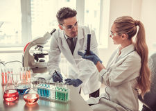 At the laboratory. Attractive young medical doctors are working with test tubes and microscope at the lab Stock Photography