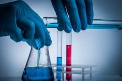 Laboratory beaker in analyst`s hand in plastic glove. Laboratory beaker in analyst`s hand in plastic glove stock photo