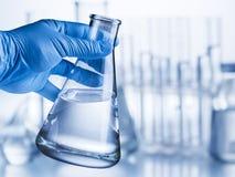 Laboratory beaker in analyst`s hand. Laboratory beaker in analyst`s hand in plastic glove stock photo