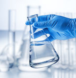 Laboratory beaker in analyst`s hand. Laboratory beaker in analyst`s hand in plastic glove royalty free stock images