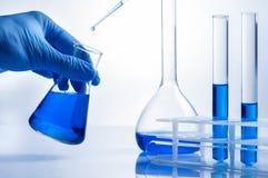 Laboratory beaker in analyst& x27;s hand in plastic glove. royalty free stock photo