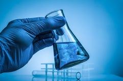 Laboratory beaker in analyst`s hand in plastic glove. royalty free stock photos
