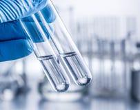 Laboratory beakers in analyst`s hand. stock photo