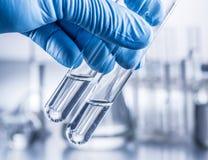 Laboratory beakers in analyst`s hand. Laboratory beakers in analyst`s hand in plastic glove royalty free stock photos