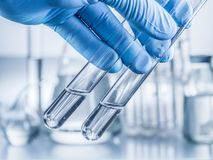 Laboratory beakers in analyst`s hand. Laboratory beakers in analyst`s hand in plastic glove royalty free stock photo