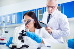 Laboratory, biotechnology, team work. Researcher is checking the. Esample on microscope and older professor is controlling her work and making notes. They are Stock Photo