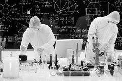 Laboratory chemical analysis. General-view  of two people manipulating laboratory tools, analysing and aplying chemical techniques  using transparent laboratory Royalty Free Stock Photo