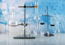 Laboratory conditions. Chemical scales, tripod with laboratory flasks and test tubes on blue. Background royalty free stock images