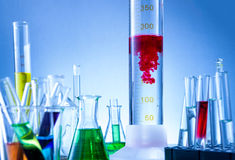 Laboratory equipment, bottles filled with colorful liquids, red liquid reacted Royalty Free Stock Images