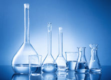 Laboratory equipment, bottles, flasks on blue background Royalty Free Stock Image