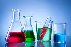 Laboratory equipment, bottles, flasks with color liquid. On blue background Stock Photos
