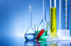 Laboratory equipment, bottles, flasks with color liquid  on blue background.  Stock Images