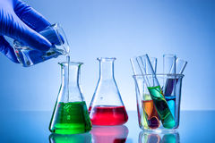 Laboratory equipment, bottles, flasks with color liquid, hand poured Royalty Free Stock Images
