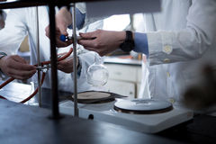 Laboratory equipment for distillation.Student/intern/technician's hands showing experiment.Working in teams for a better result.Sc Stock Images