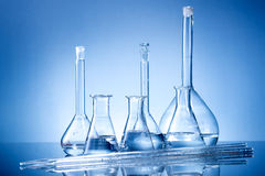 Laboratory equipment, glass flasks, pipettes on blue background Royalty Free Stock Photo