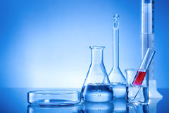 Laboratory equipment, glass flasks, pipettes, red liquid. On blue background Stock Photo