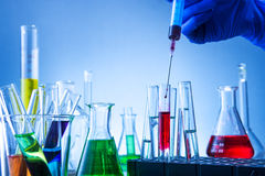 Laboratory equipment, lots of glass filled with colorful liquids and hand injection Stock Photos