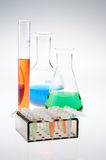 Laboratory equipment with multicolored liquid. Assorted laboratory glassware (cylinder, beaker, flask) and plastic tubes with multicolored liquid Stock Image