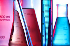 Laboratory Equipment in Science Research Lab. Scientific laboratory graduated cylinder filled with blue liquid and conical Erlenmeyer flasks full of aqua and Royalty Free Stock Images