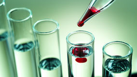 Laboratory equipment, in test tubes drops red liquid Royalty Free Stock Photo