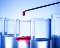 Laboratory equipment, in test tubes drops red liquid Stock Image