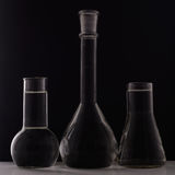 Laboratory equipment, three glass flask on black background Stock Photos